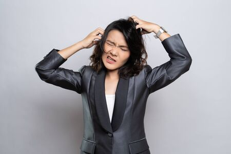 Businesswoman scratching her head isolated over white background Stock Photo