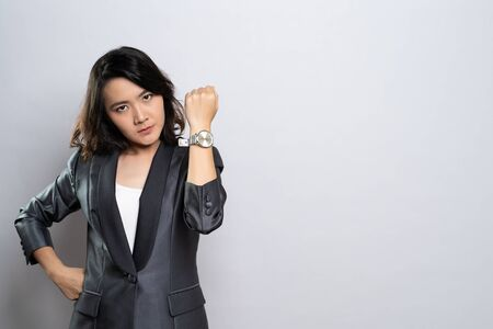 Angry woman pointing at her watch Stock Photo