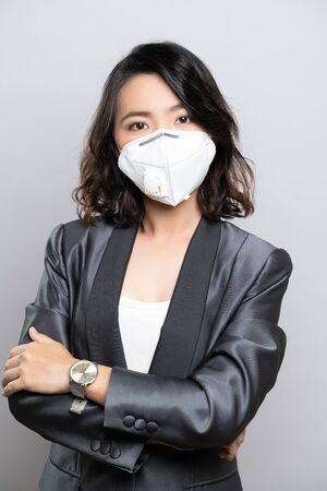 Femme d'affaires portant le masque N95 isolé sur fond blanc