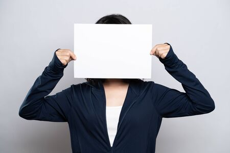 Portrait of a healthy woman showing paper cover her face isolated over white background