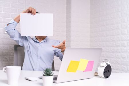 Woman sitting at home office and showing blank paper cover her face Фото со стока