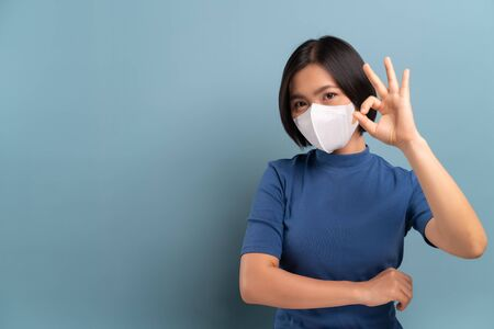 Portrait of asian woman wearing the hygienic mask isolated on blue Stock Photo