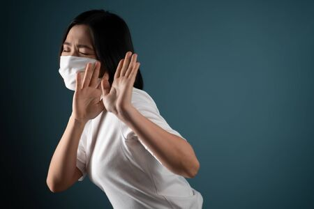 Don't touch me. Asian woman wearing hygiene mask panic and disguted showing hand stop sign and standing isolated over blue background. Health care concepts.