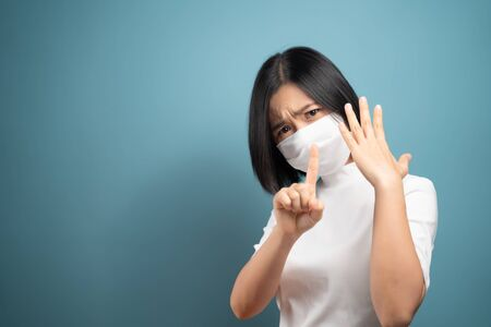 Don't Touch Your Face. Asian woman wearing hygiene mask showing hand stop sign and standing isolated over blue background. Health care concepts.