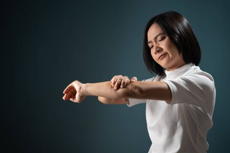 Asian woman was sick with body pain office syndrome and standing isolated over blue background. Health care concepts. Фото со стока