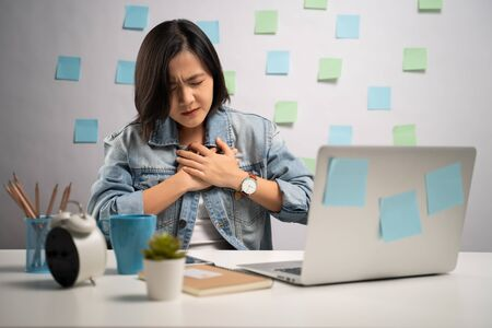 Asian woman working on a laptop was sick with chest pain sitting at home office. WFH. Work from home. Prevention Coronavirus COVID-19 concept.