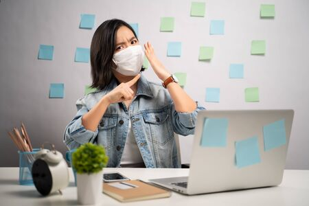 Don't Touch Your Face. Asian woman wearing protective face mask showing hand making stop sign at home office. WFH. Work from home. Prevention Coronavirus COVID-19 concept.