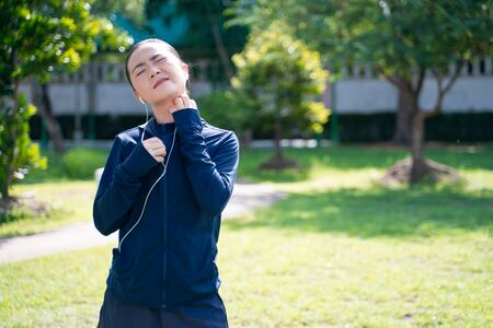 Portrait of Asian woman wearing earphones listening to music was sick with irritate itching her skin at park. Woman exercise at park itching her skin.