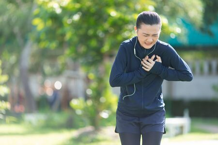 Portrait of Asian woman wearing earphones listening to music was sick with chest pain at park. Woman exercise at park suffering from painful chest.