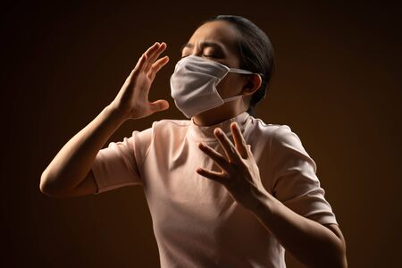 Asian woman wearing protective mask for protection from virus and disease coughing standing isolated on beige background. Low key.