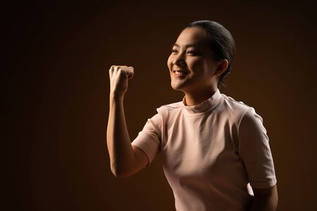Asian woman happy confident standing showing her fist make a winning gesture isolated on beige background. Low key.