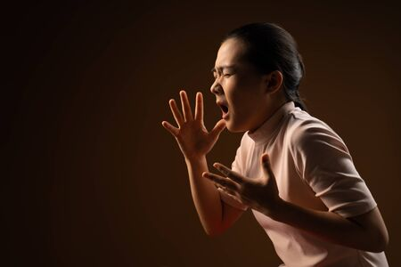 Asian woman was sick with sore throat, coughing sneezing and standing isolated on beige background. Low key