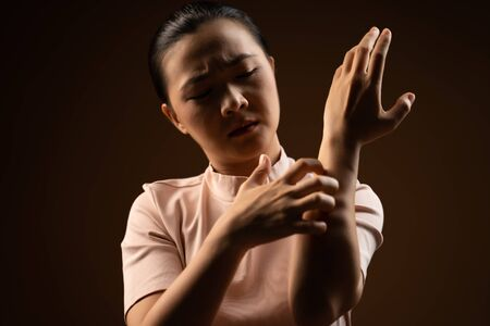 Asian woman was sick with irritate itching her skin, scratching her skin, standing isolated on beige background.Low key.