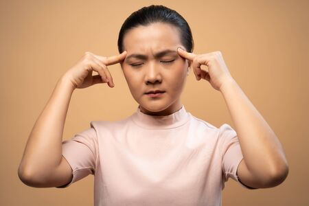 Asian woman was sick with headache touching her head and standing isolated on beige background.