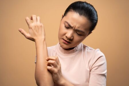 Asian woman was sick with irritate itching her skin, scratching her skin, standing isolated on beige background. Foto de archivo