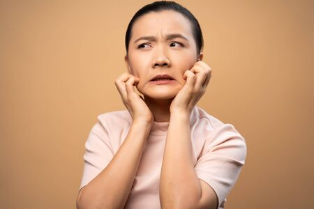 Asian woman was sick with irritate itching her skin, scratching her skin, standing isolated on beige background.