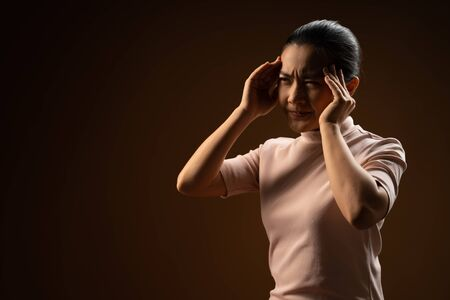 Asian woman was sick with headache touching her head and standing isolated on beige background. Low key.