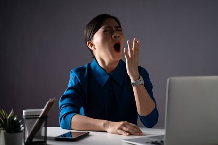 Asian woman in blue shirt tired and sleepy, yawning at office. isolated on white background. Low key. Banque d'images