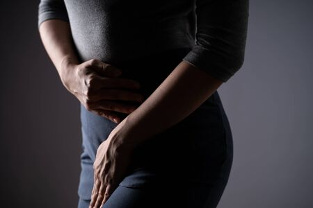 Closeup shot of woman having painful holding hands pressing her crotch lower abdomen isolated on background. Low key. Stockfoto