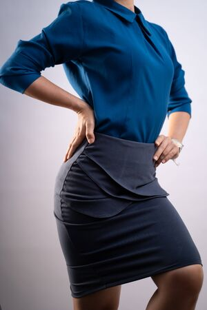 Body shape of woman in blue shirt posing showing her body isolated on background. Closeup  shot.