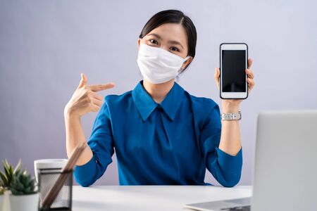 Asian woman in blue shirt wearing protective face mask showing blank screen of smart phone and working on a laptop at office. isolated on white background.