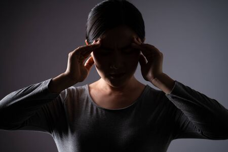 Asian woman was sick with headache touching her head and standing isolated on background. Low key.