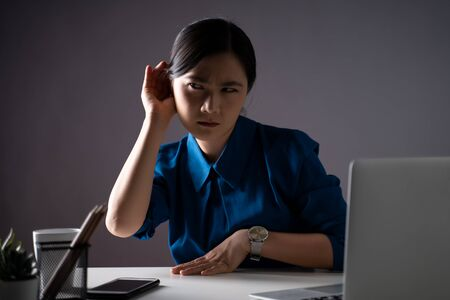 Asian woman holds her hand near ear and listens carefully at office. isolated on background. Low key. Banque d'images