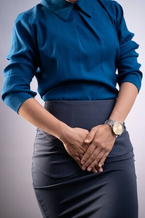 Closeup shot of woman having painful holding hands pressing her crotch lower abdomen isolated on background