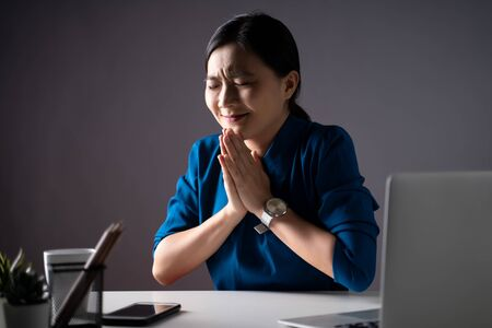 Asian woman happy in blue shirt holding hands in prayer, looking at copy space, working on a laptop at office. isolated on background. Low key. 版權商用圖片