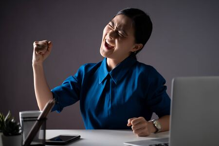 Asian woman happy in blue shirt make winning gesture working on a laptop at office. isolated on white background. Low key.