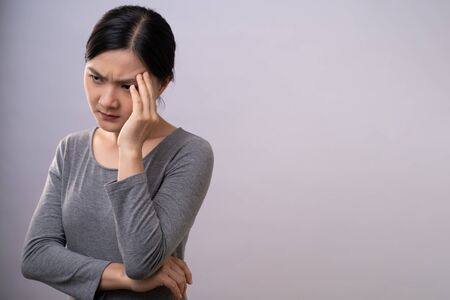 Asian woman was sick with headache touching her head and standing isolated on background.