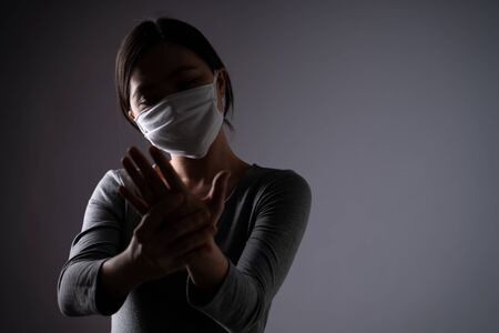 Asian woman was sick with body pain touching her body and standing isolated on background. Low key.