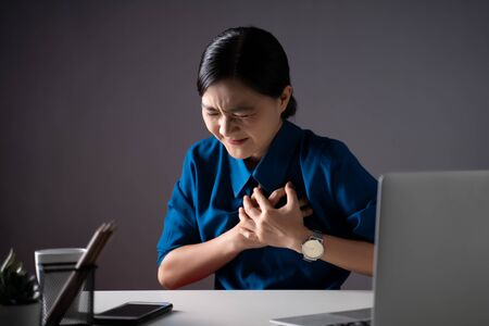 Asian woman in blue shirt working on a laptop was sick with chest pain sitting at office. isolated on white background. Low key. 版權商用圖片