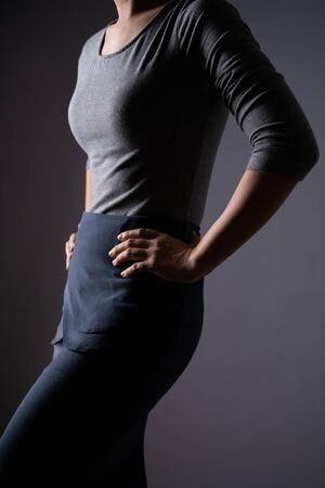 Body shape of woman in blue shirt posing showing her body isolated on background. Closeup  shot. Low key.