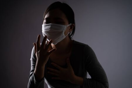 Asian woman wearing protective face mask was sick with sore throat standing isolated on background. Low key. Imagens - 150414222