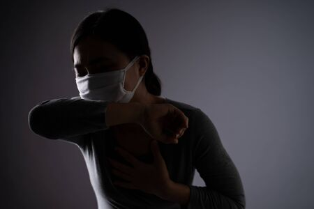 Asian woman wearing protective face mask was sick with sore throat standing isolated on background. Low key. Imagens - 150414225