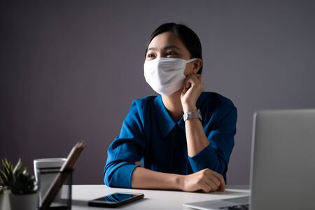 Asian woman wearing protective face mask working on a laptop at office. WFH. Work from home. Prevention Coronavirus COVID-19 concept. Low key.