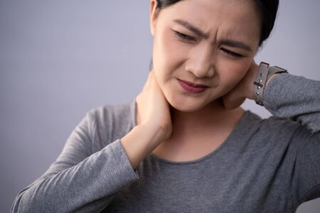 Asian woman was sick with body pain touching her body and standing isolated on background.