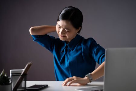 Asian woman in blue shirt working on a laptop was sick with body pain sitting at office. isolated on white background. Low key. Imagens