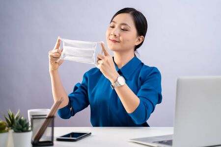 Asian woman in blue shirt wearing protective face mask working on a laptop sitting at office. isolated on white background. Imagens - 150414239