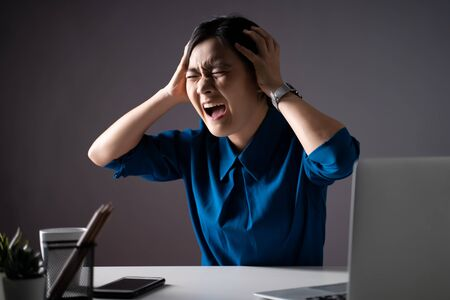 Asian woman in blue shirt angry and shouting, at office. isolated on background. Low key. Imagens
