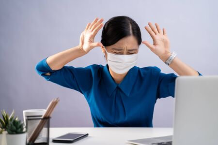 Don't Touch me. Asian woman in blue shirt wearing protective face mask, panic disgusted and showing hand stop sign at office. isolated on white background. Imagens - 150414246
