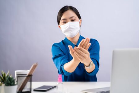 Asian woman in blue shirt wearing protective face mask washing hands using hand sanitizer gel and working on a laptop at office. isolated on white background.