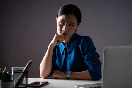 Asian woman in blue shirt feel confused, looking at copy space, working on a laptop at office. isolated on background. Low key. Imagens