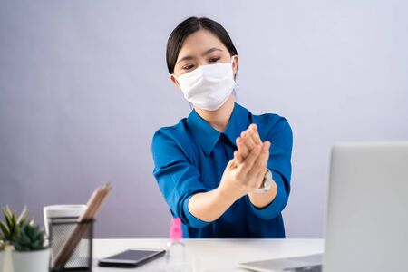 Asian woman in blue shirt wearing protective face mask washing hands using hand sanitizer gel and working on a laptop at office. isolated on white background. Imagens - 150414252