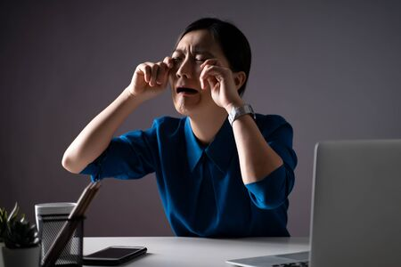 Asian woman in blue shirt sad and crying, working on a laptop at office. isolated on background. Low key.
