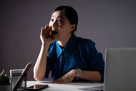 Asian woman happy holds her hand near mouth and shouting at office. isolated on background. Low key.
