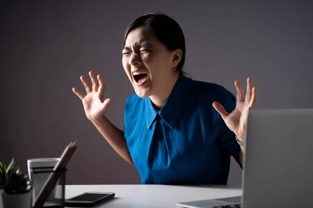 Asian woman in blue shirt angry and shouting, at office. isolated on background. Low key. Imagens - 150414255