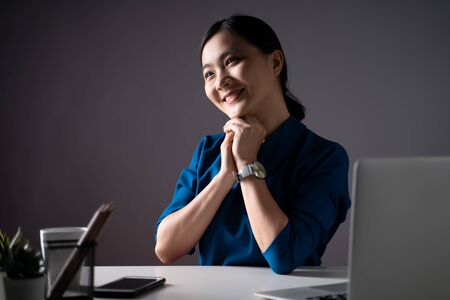 Asian woman happy smiling in blue shirt looking at copy space, working on a laptop at office. isolated on white background. Low key.