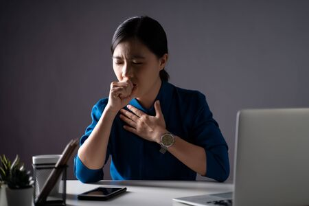 Asian woman in blue shirt was sick with fever, working on a laptop at office. isolated on white background. Low key. Imagens - 150414259